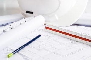 Biały kask ochronny oraz plany architektoniczne leżące na blacie