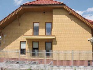 Żółty budynek mieszkalny z czerwonym dachem